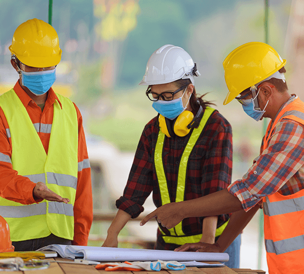 Construction workers wearing masks while working.