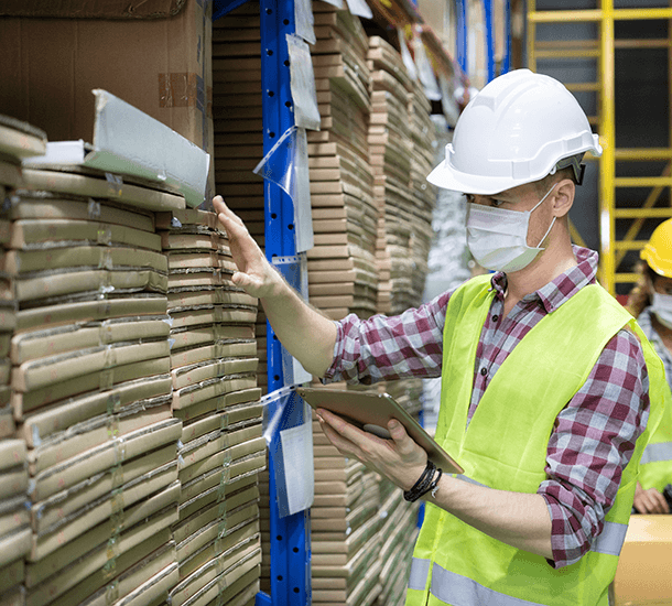 Worker in a warehouse during COVID-19 wearing a mask.